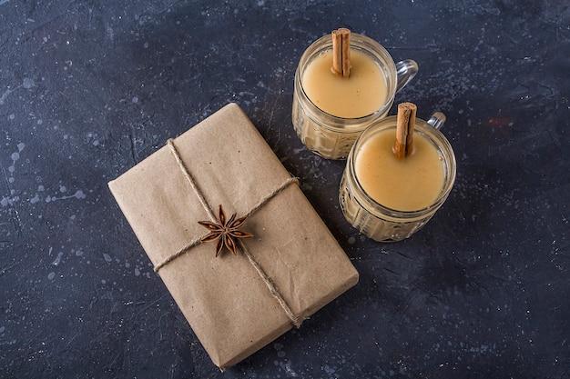 Традиционный американский и кандакский рождественский напиток гоголь-моголь в хрустальных бокалах с корицей или мускатным орехом. подарочная коробка на новый год
