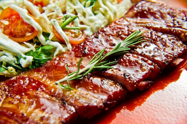 Traditional american barbecue pork ribs with a side dish of green salad.