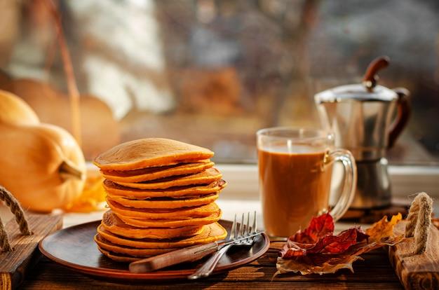 カボチャのパンケーキと窓にコーヒーの伝統的なアメリカの朝食。