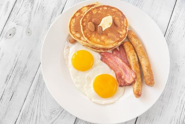 Традиционный американский завтрак с яйцами, сосисками, блинами и беконом