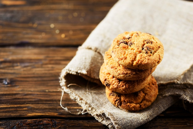 Traditional american cookies with chocolate, wooden table, selective focus and copyspace