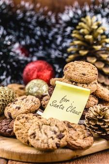 英語のメモが付いている伝統的なアメリカのクッキー:サンタクロースのために。バックグラウンドでのクリスマスの装飾