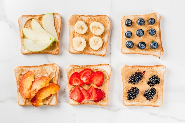 Traditional american and european summer breakfast: sandwiches of toast with peanut butter, berry, fruit apple, peach, blueberry, blueberry, strawberry, banana. white marble table. copyspace top view