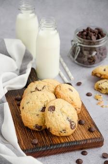 ミルクとストローのボトルと灰色の背景に古い木の板にチョコレートチップと伝統的なアメリカの手作りクッキー。垂直方向。上面図。