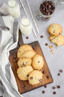 ミルクとストローのボトルと灰色の表面に古い木の板にチョコレートチップと伝統的なアメリカの自家製クッキー。垂直方向。上面図。