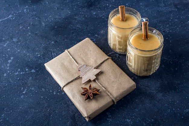 Traditional american and kandacian christmas drink eggnog in crystal glasses with cinnamon or nutmeg. gift box for the new year decorated with anise star.