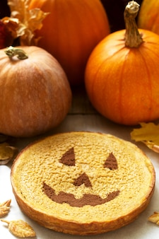 Traditional american pumpkin homemade cake decorated with cocoa, pumpkins and autumn leaves.
