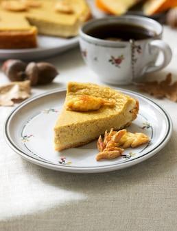 Традиционный американский тыквенный домашний торт, украшенный печеньем на фоне тыквы и осенних листьев.