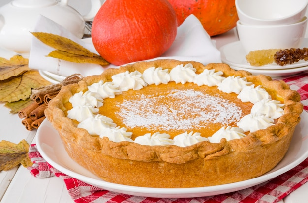 伝統的なアメリカのカボチャは、白い皿にクリームパイをホイップしました。感謝祭のケーキ。