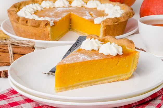 白いプレートに伝統的なアメリカのカボチャホイップクリームパイ