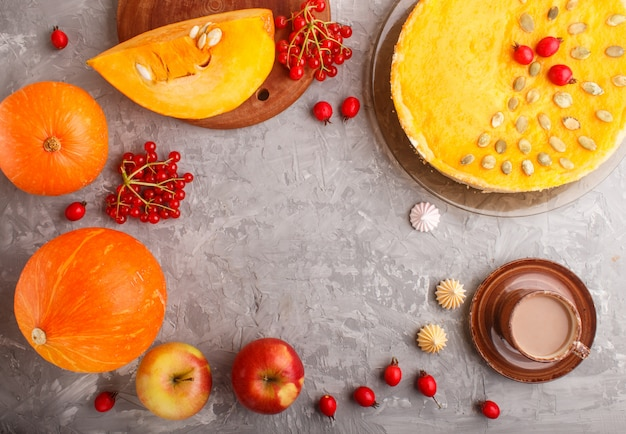 Traditional american sweet pumpkin pie decorated with hawthorn red berries and pumpkin seeds with cup of coffee on a gray concrete background