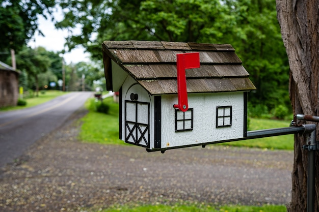 A traditional american wooden mailbox that looks like a cottage, on the side of a village road  in penfield, ny