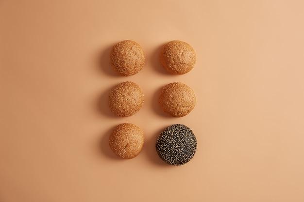 베이지 색 배경에 고립 된 두 행으로 배열 된 추가하지 않고 참깨와 전통 및 1 개의 검은 오징어 잉크 버거 빵. 수제 햄버거 빵. 건강에 해로운 길거리 음식 개념
