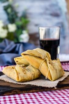 伝統的なアンデスのトウモロコシと肉のタマーレは、グラスワインとともに静物テーブルの木製ボードで提供されます。郷土料理。コピースペース。