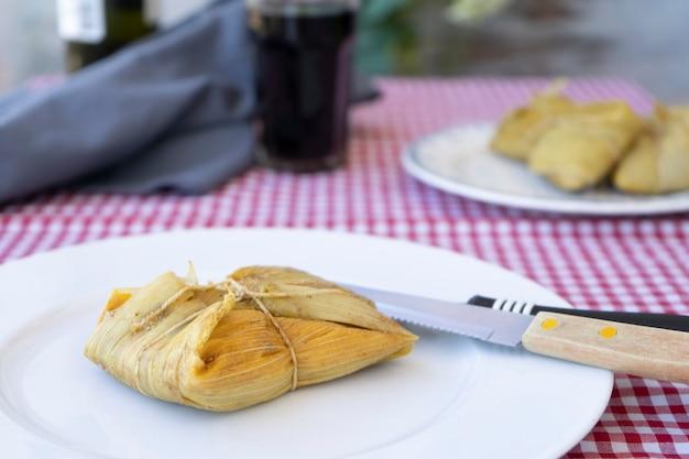伝統的なアンデスのトウモロコシと肉のタマーレを、ワインと一緒に静物テーブルの木製ボードで提供