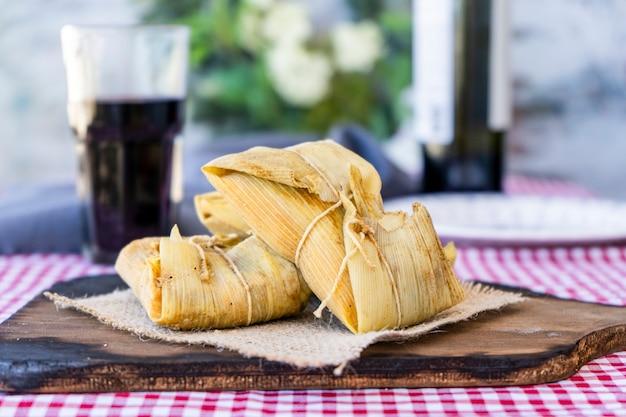 伝統的なアンデスのトウモロコシと肉のタマーレは、静物テーブルの木製ボードで提供されます