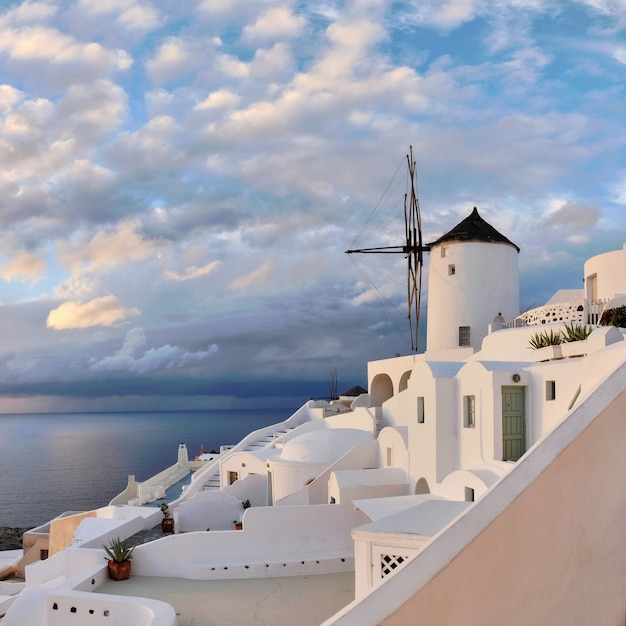Traditional apartments and windmill in oia village on a sunset, panoramic image.