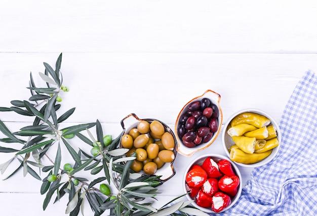 Традиционные закуски, зеленые и красные оливки из греческой кухни. свежие ветки маслин. copyspace. выше. синяя клетчатая скатерть