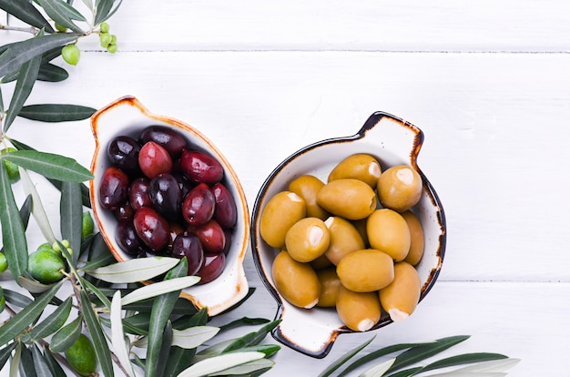 Traditional appetizers, green and red olives from greek cuisine. white wood background. fresh branches of olives. copy space