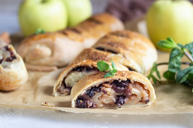 Traditional apple strudel with raisin and cinnamon on grey concrete