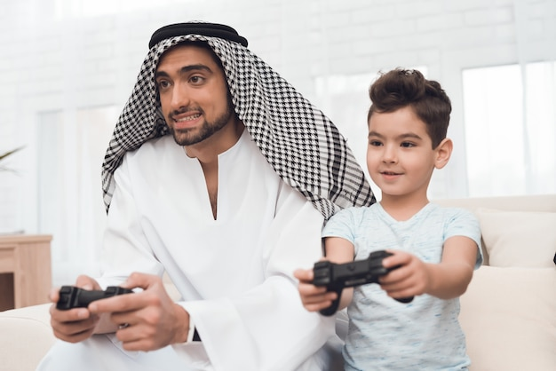 A traditional arab family plays a game console.
