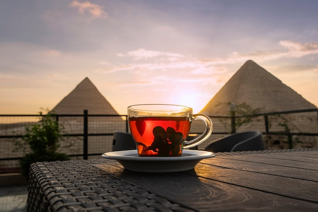 Traditional arab tea in a glass against the background of the great pyramids of giza. beautiful view of the attraction in the restaurant at sunset. the sun sets behind the pyramids