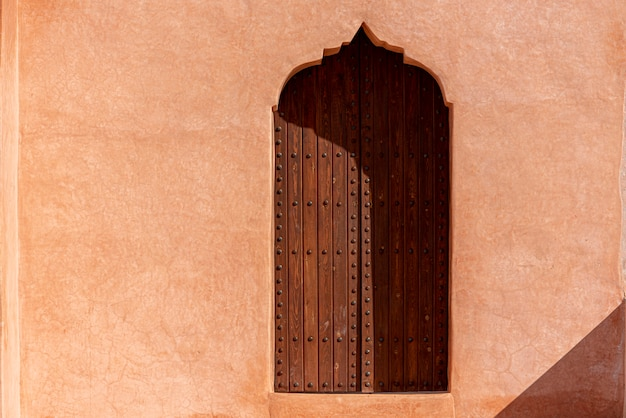 Traditional arabian architecture, muslim style wooden door and red clay wall