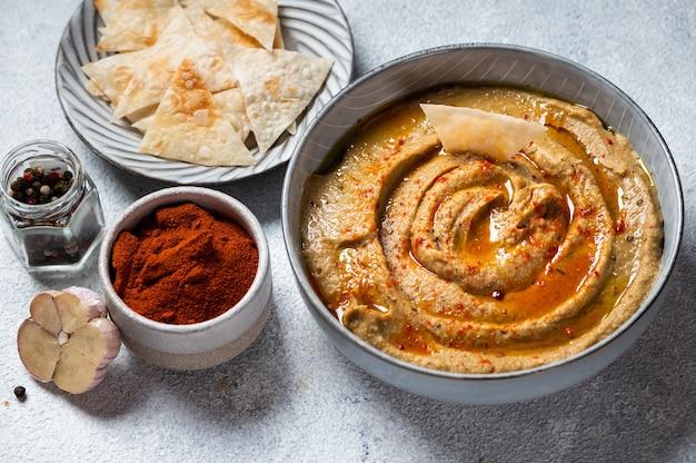 Традиционный арабский соус баба гануш из баклажанов с травами и копченой паприкой на светлом фоне. хумус из баклажанов. бабагануш или икра баклажанная. запеченный баклажан. соус из баклажанов по-турецки