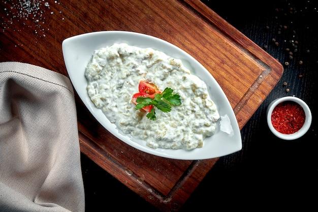 木製のテーブルに白いヨーグルトにオリーブオイルとハーブを添えた伝統的なアラビアのナス料理ババガヌーシュ