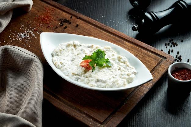 Традиционное арабское блюдо из баклажанов баба гануш с оливковым маслом и зеленью в белом йогурте. деревянный стол. закрыть вверх