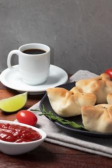 伝統的なアラビアの肉のエスフィーハにコーヒーを添えて。