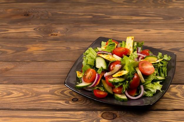 Традиционный арабский салат фаттуш на тарелке на деревянном фоне.