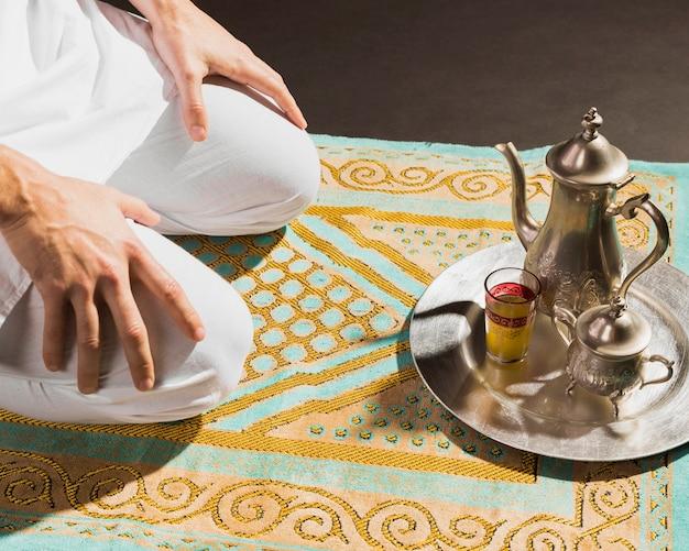 伝統的なアラビアの熱いお茶と座っている男