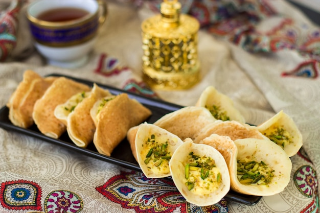 Traditional arabic kataif crepes stuffed with cream and pistachios, prepared for iftar in ramadan, oud in gold, on paisley