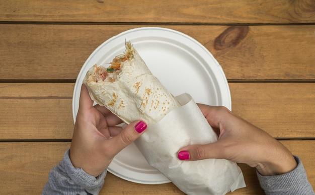 Traditional arabic street food - doner kebab in female hands