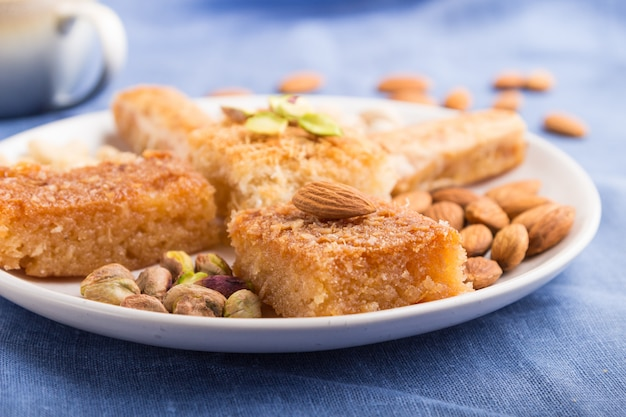 Traditional arabic sweets (basbus, kunafa, baklava), a cup of coffee and nuts on a gray concrete surface  side view, selective focus.