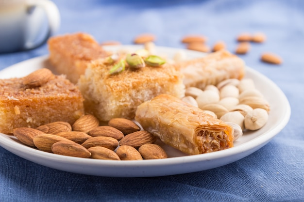 Traditional arabic sweets (basbus, kunafa, baklava), a cup of coffee and nuts  side view