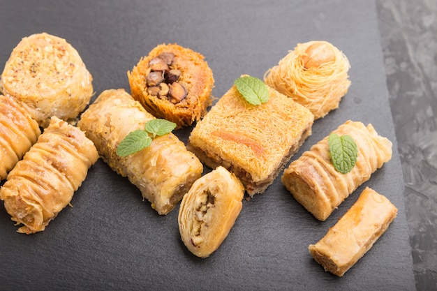 Traditional arabic sweets on a black slate board on a black concrete surface. side view, selective focus.