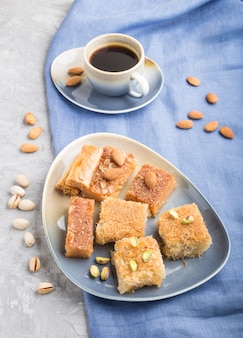 Traditional arabic sweets and a cup of coffee on a gray concrete background. side view, close up.