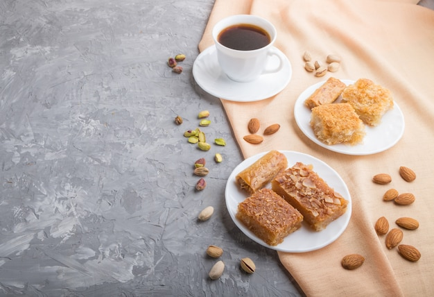Traditional arabic sweets and a cup of coffee on a gray concrete background. side view, copy space.