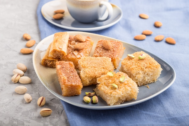 Traditional arabic sweets and a cup of coffee on a gray concrete background. side view, selective focus.