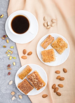 Traditional arabic sweets and a cup of coffee on a gray concrete background.  top view, close up.