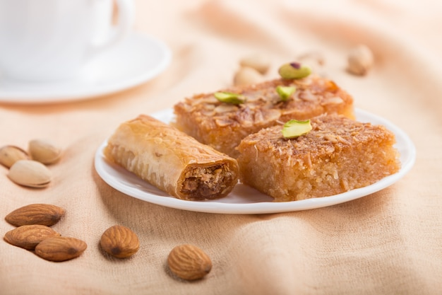 Traditional arabic sweets and a cup of coffee on a gray concrete surface. side view, selective focus, macro.