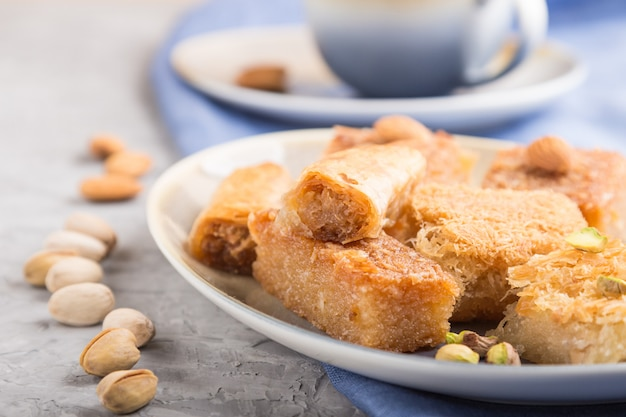 Traditional arabic sweets and a cup of coffee on a gray concrete surface. side view, selective focus.