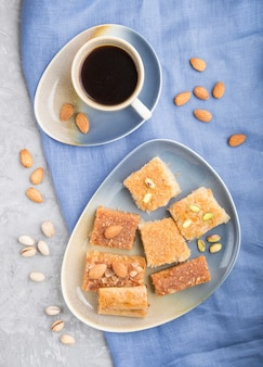 Traditional arabic sweets and a cup of coffee on a gray concrete surface.  top view, close up.