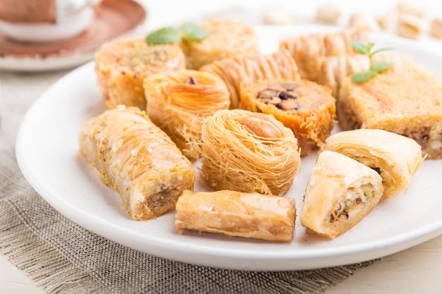 伝統的なアラビアのお菓子(クナファ、バクラヴァ)と白い木製の背景の上にコーヒーを1杯。側面図、セレクティブフォーカス。