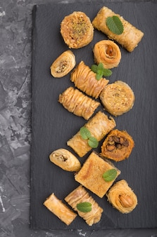 Traditional arabic sweets (kunafa, baklava) on a black slate board on a black concrete background.top view, close up.