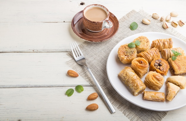 Traditional arabic sweets (kunafa, baklava)  and a cup of coffee on a white wooden surface. side view, copy space.