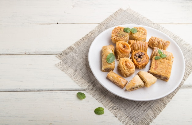 Traditional arabic sweets (kunafa, baklava) on a white wooden surface. side view, copy space.