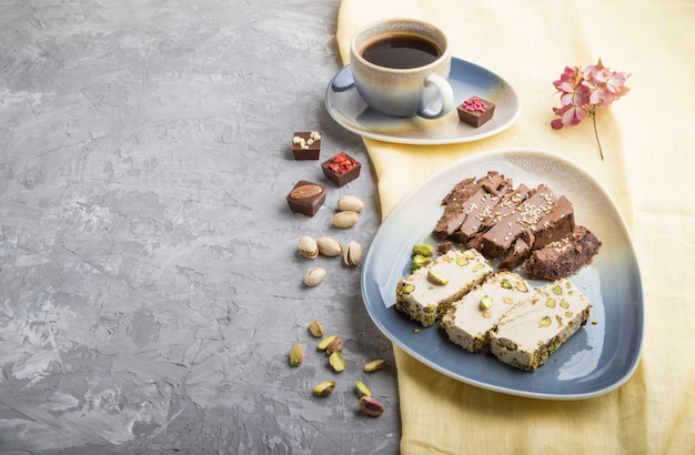 Traditional arabic sweets sesame halva with chocolate and pistachio and a cup of coffee on a gray concrete background, side view, copy space.